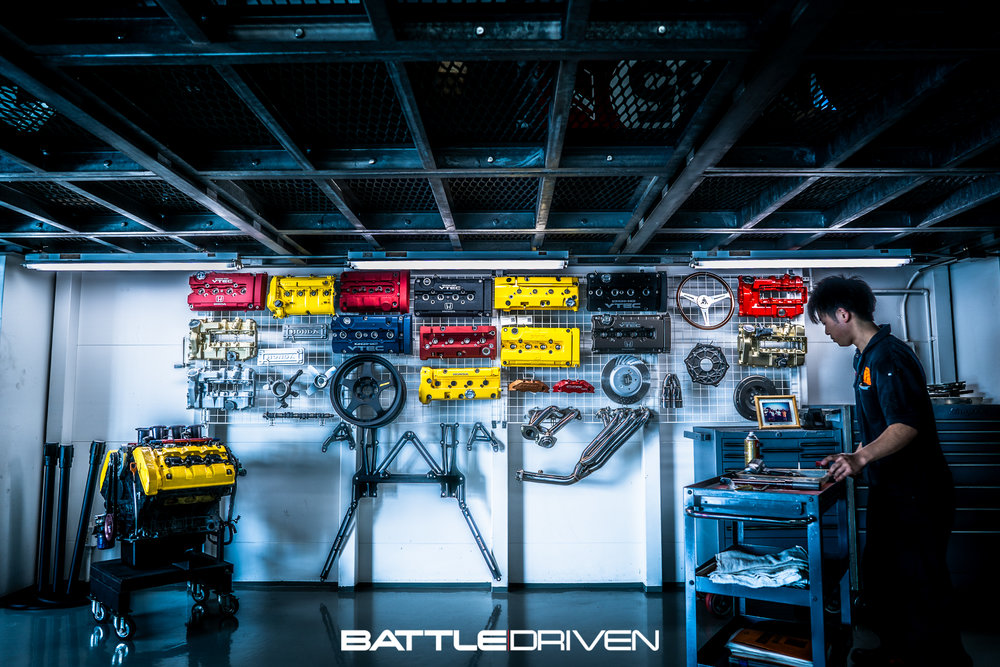 Wall display of various valve covers, cams, headers, rotors, individual throttle bodied NSX motor, etc.