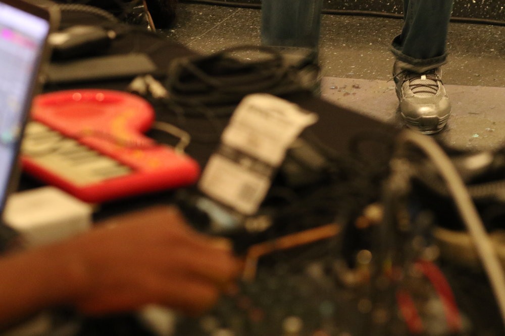 In the blurred foreground, Devin twists nobs on an arrangement of sound equipment while, in the in-focus background, my feet tap dance in the silver  sneakers on the sheet of plexiglass.