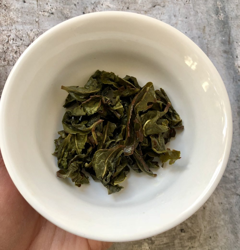 Pictured here is the infused leaves of the lightly oxidized  Jade Oolong  tea. It is noticeable that the edges of the leaves are bruised while the overall appearance of the leaves remained green.