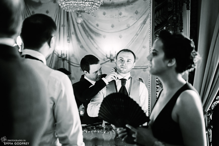 Bestman fixes groom's tie in the mirror of the Palais Eynard