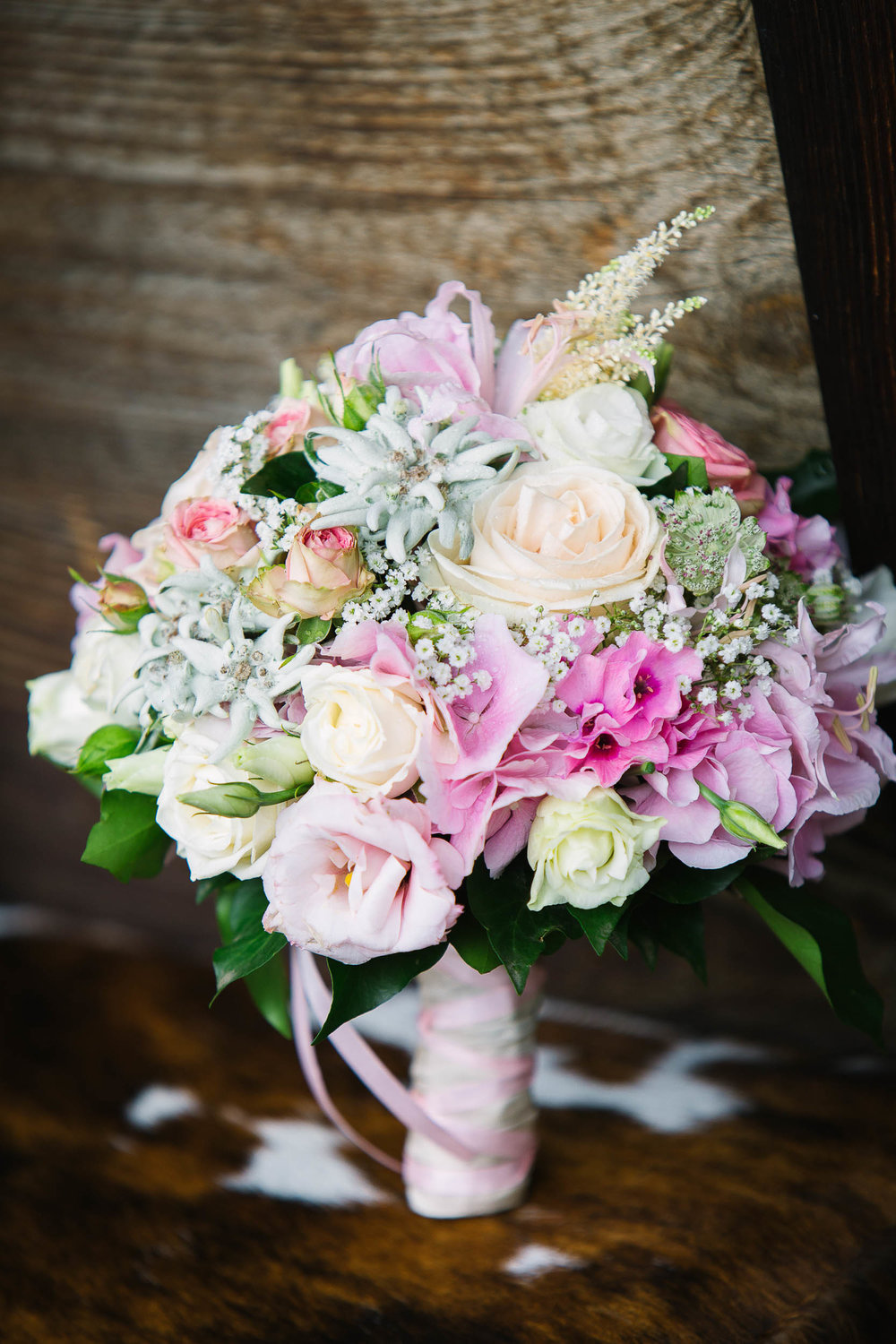 An elegant pink pastel wedding bouquet with edelweiss and roses