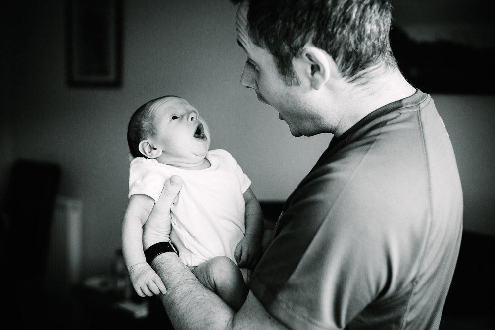 Father imitates his newborn baby yawning, photo in black and white by Emma Godfrey.