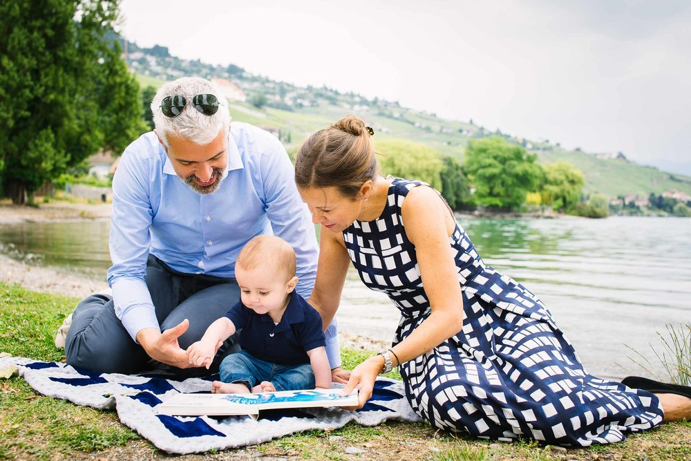 Parents read to 6 month old baby boy on shore of Lake.