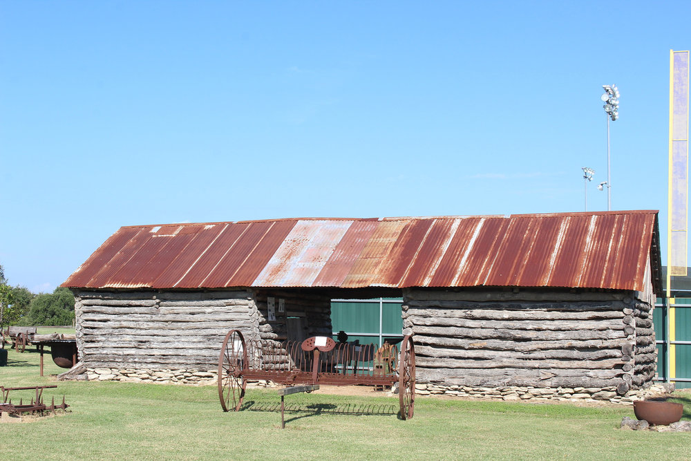 The authentic circa 1904 double-log corn crib with dog trot was constructed with hand-hewn logs joined with simple saddle notching. A central passageway allowed for easy loading/unloading of wagons to or from a crib on either side. The Log Crib was donated by Hilda Fajkus and Sylvia Ratcliffe of Cistern. It was moved to the site by Kana Brothers Moving Company and restored by brothers Ed, Ernest, David, and Robert Vasek of Plum, and Robert Stall of Smithville with replacement logs donated by Vickie Matocha and Jeb Pape.