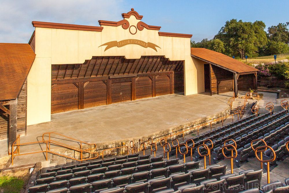 Thanks to an initial grant by the LCRA and a matching grant by La Grange resident Sanford Schmid, the amphitheater was built in 2000. The 5,500-square-foot facility is built in a Texas Czech style and includes an open stage, dressing/meeting rooms, restrooms, and prop storage area. Music is very special in the life of Czechs. The Czech saying Muziky, Muziky (Music, Music)adorns the top of the stage. The facility is available for rent and used for musical performances, theatrical plays, presentations, and outdoor weddings.