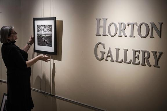 Curator Lynda Dalton-Gallagher hangs the show