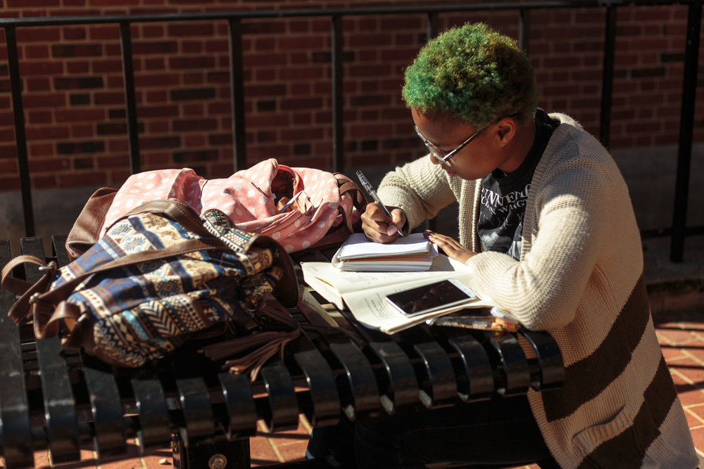 Jakera Webb, a junior Japanese major, works on homework in a courtyard between the Health Center and the Jimenez  buildings. Finding time to concentrate on homework can be hard, but is necessary for a successful school year.