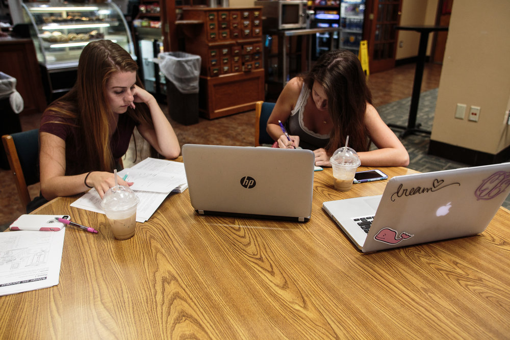 Emily Bichard (left), a sophomore Art education major, and Casey Tarman (right), a sophomore applied math major, drink coffee and study in the McKeldin Library cafe, Footnotes.