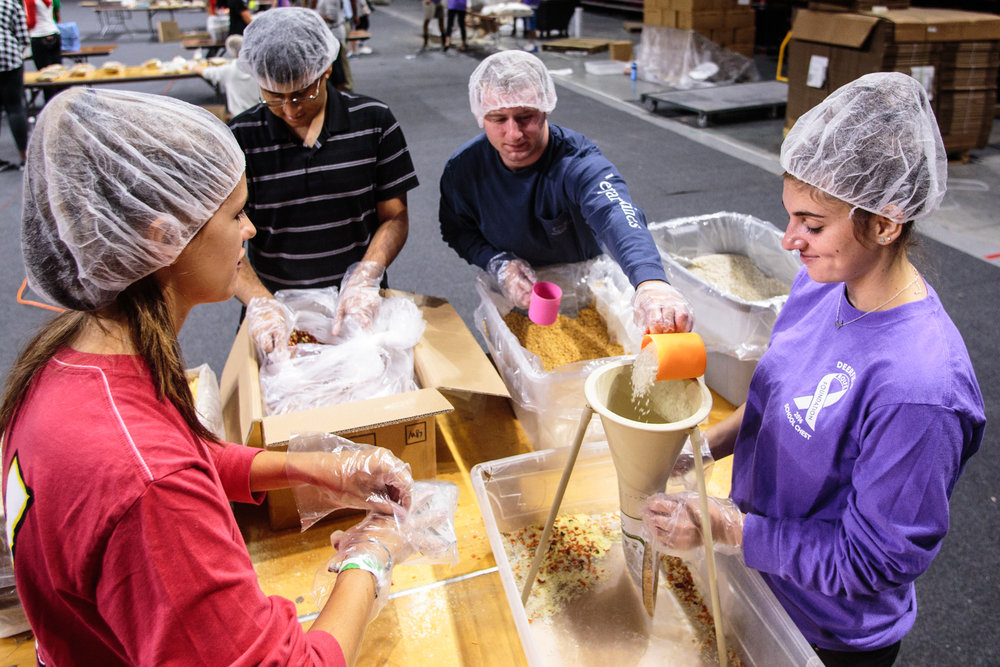Volunteers help pack food at the Terps Against Hunger homecoming event. The event, held Sunday in the Xfinity center, featured the organization's one millionth packed meal for underprivilged families in the D.C. area.