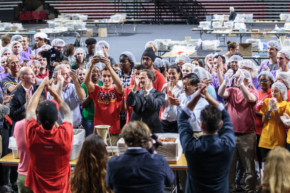 Joshua Turskey holds high the one millionth packaged meal at the Terps Against Hunger homecoming event held in the Xfinity Center on Sunday, Sept. 25, 2016.