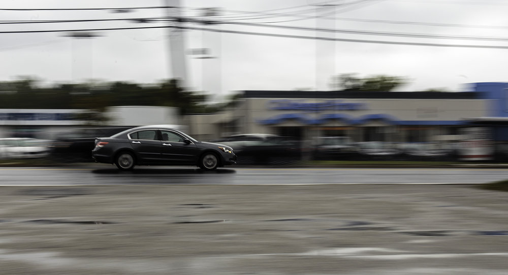 A car drives along Route 1 on Saturday, Oct. 8, 2016. By panning along with the movement of the car, the background seems blurred while the vehicle stays (somewhat) sharp.