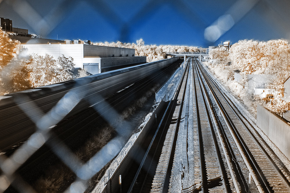 A freight train travels along the tracks.In order to slow down my shutter, a majority of these images were shot with an Infrared filter, the colors look off in this image as it is processed through an infrared false-color technique.