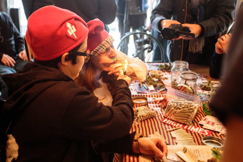 Natalie de Leon, 26 (left), helps light a marijuana joint for fellow DCMJ volunteer RachelRamone Donlan, 45 (right), at a rolling party on Thursday, Jan. 19, 2017. The D.C.-based marijuana legalization group is planning to protest President-elect Donald Trump's stated opposition to federal legalization of marijuana by passing out over 4,200 joints at Friday's inauguration. (Tom Hausman/Capital News Service via AP)