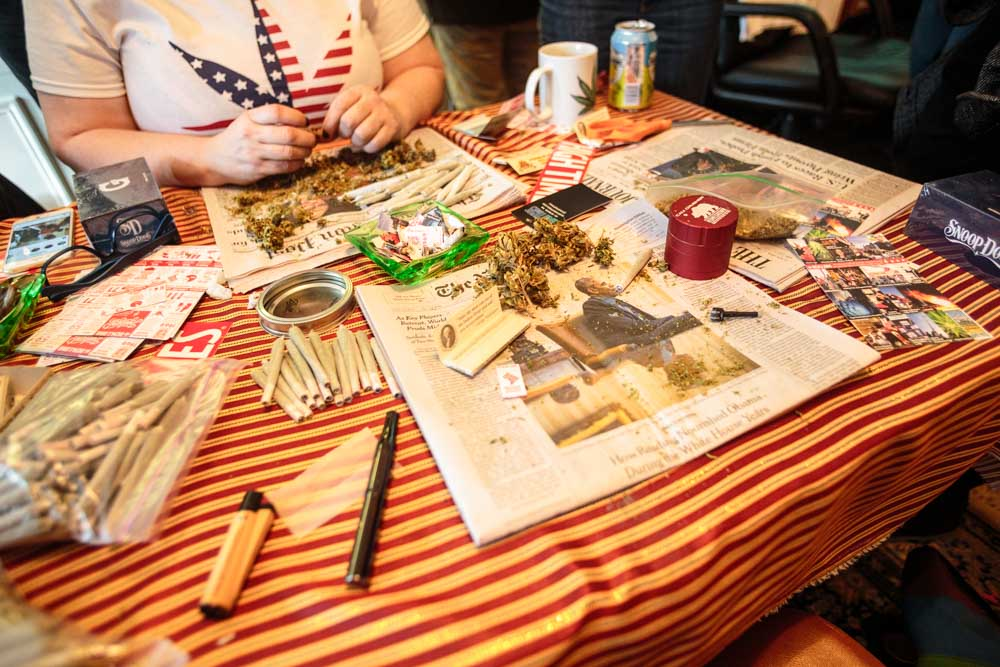 DCMJ volunteer Elizabeth Croydon, 46, rolls a joint at a table in the organization's headquarters on Thursday, Jan. 19, 2017. The D.C.-based marijuana legalization group is planning to protest President-elect Donald Trump's stated opposition to federal legalization of marijuana by passing out over 4,200 joints at Friday's inauguration.    (Tom Hausman/Capital News Service via AP)