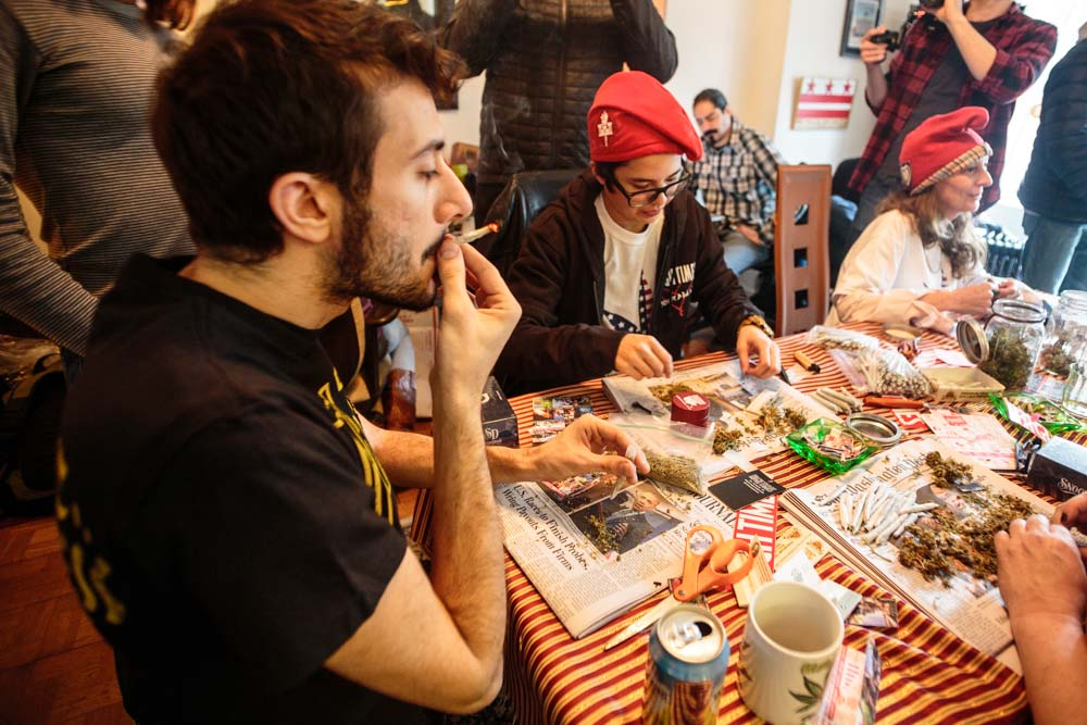DCMJ volunteer Seth Kaye, 26 (left), smokes a joint at a rolling party held in the organization's headquarters building on Thursday, Jan. 19, 2017. The D.C.-based marijuana legalization group is planning to protest President-elect Donald Trump's stated opposition to federal legalization of marijuana by passing out over 4,200 joints at Friday's inauguration.    (Tom Hausman/Capital News Service via AP)
