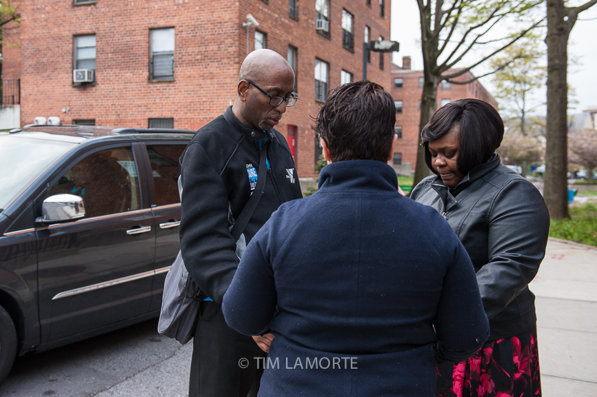 John Thompson, Lourdes Delacruz and Tania Bell-Yates of the Yonkers YMCA pray at Cottage Place Gardens on April 30.