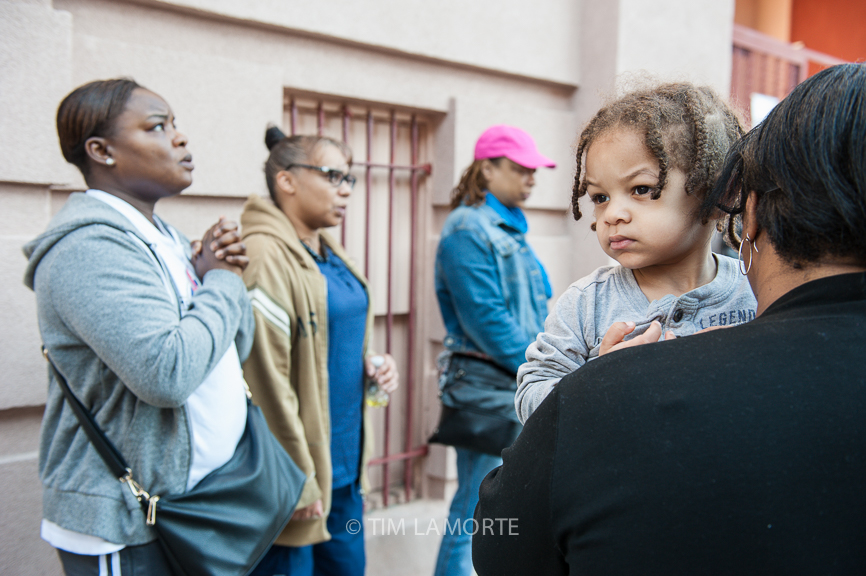 Crystal Fitzgerald (right) holds her 2-year-old son, Elijah, during a prayer outside the InnerFaith Church on Hamilton Avenue on May 14.