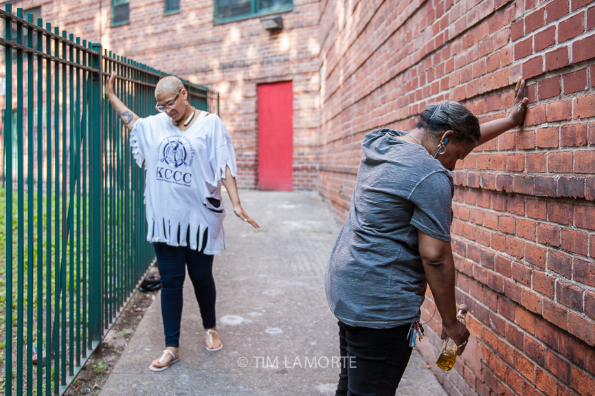 Yolanda Emery and Robbin Kittrell pray at the Ross F. Calcagno public housing complex on May 28.
