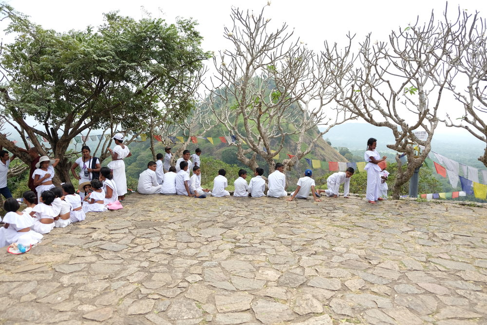 Children sitting outside the Dambulla cave temples.