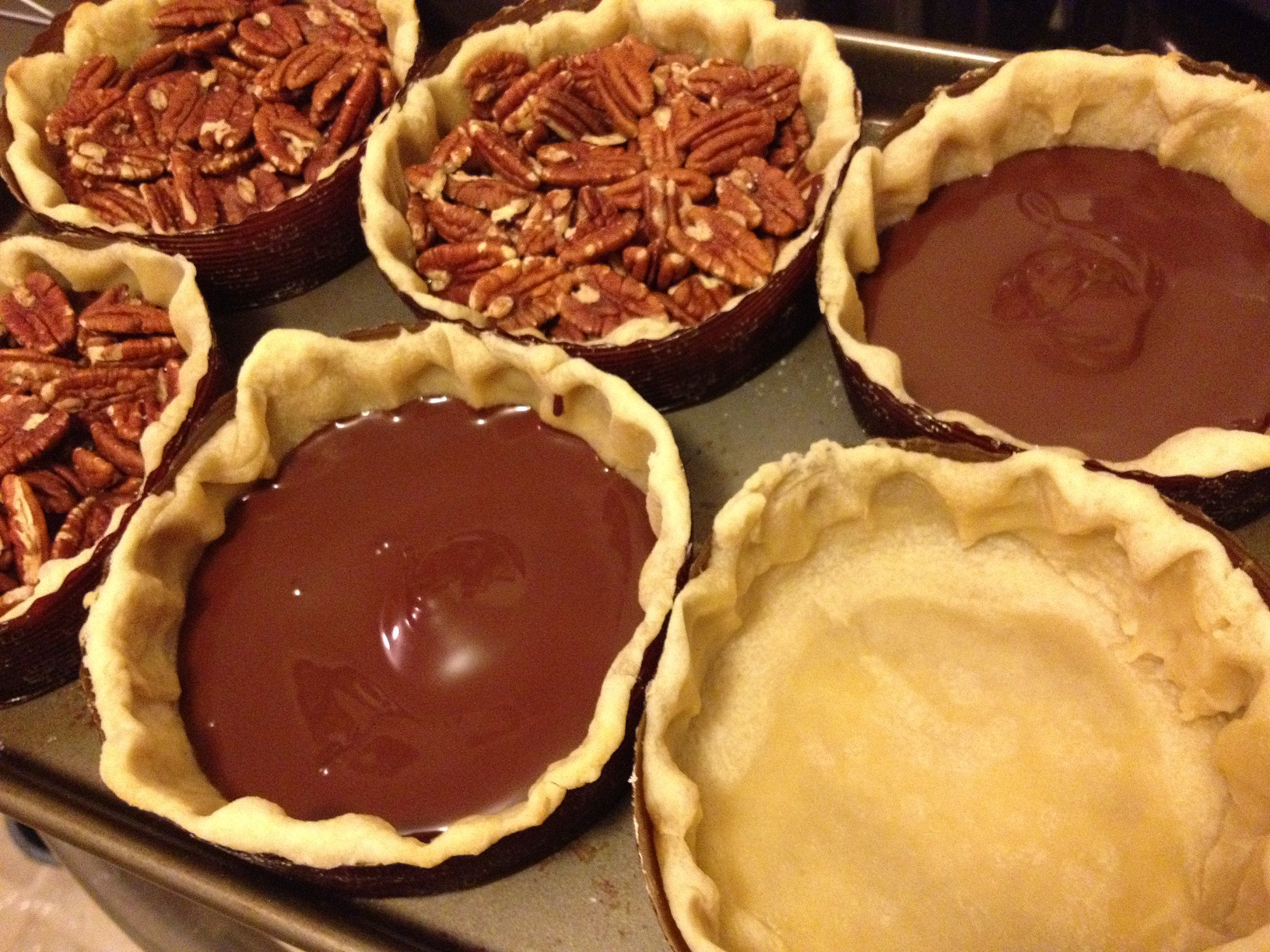 Pare baked pie shells, melted chocolate layer, and toasted pecans