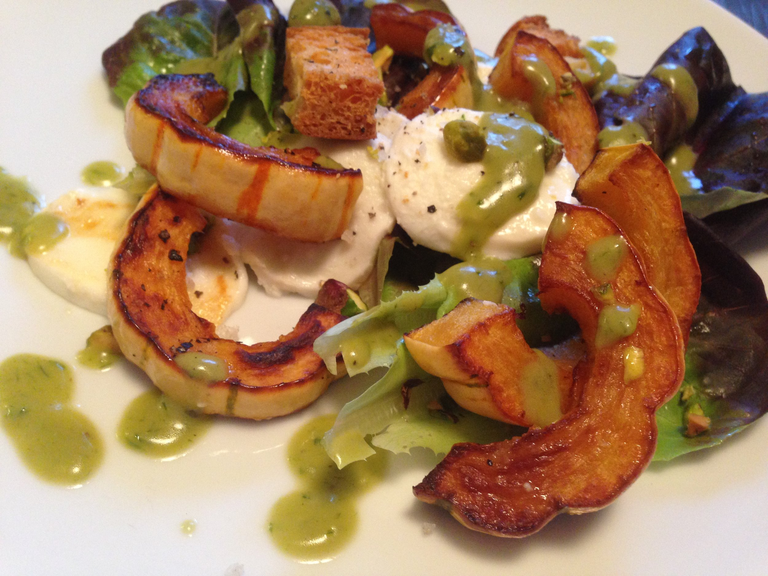 Plated Roasted Squash Salad with Chive Dressing drizzled over the top.