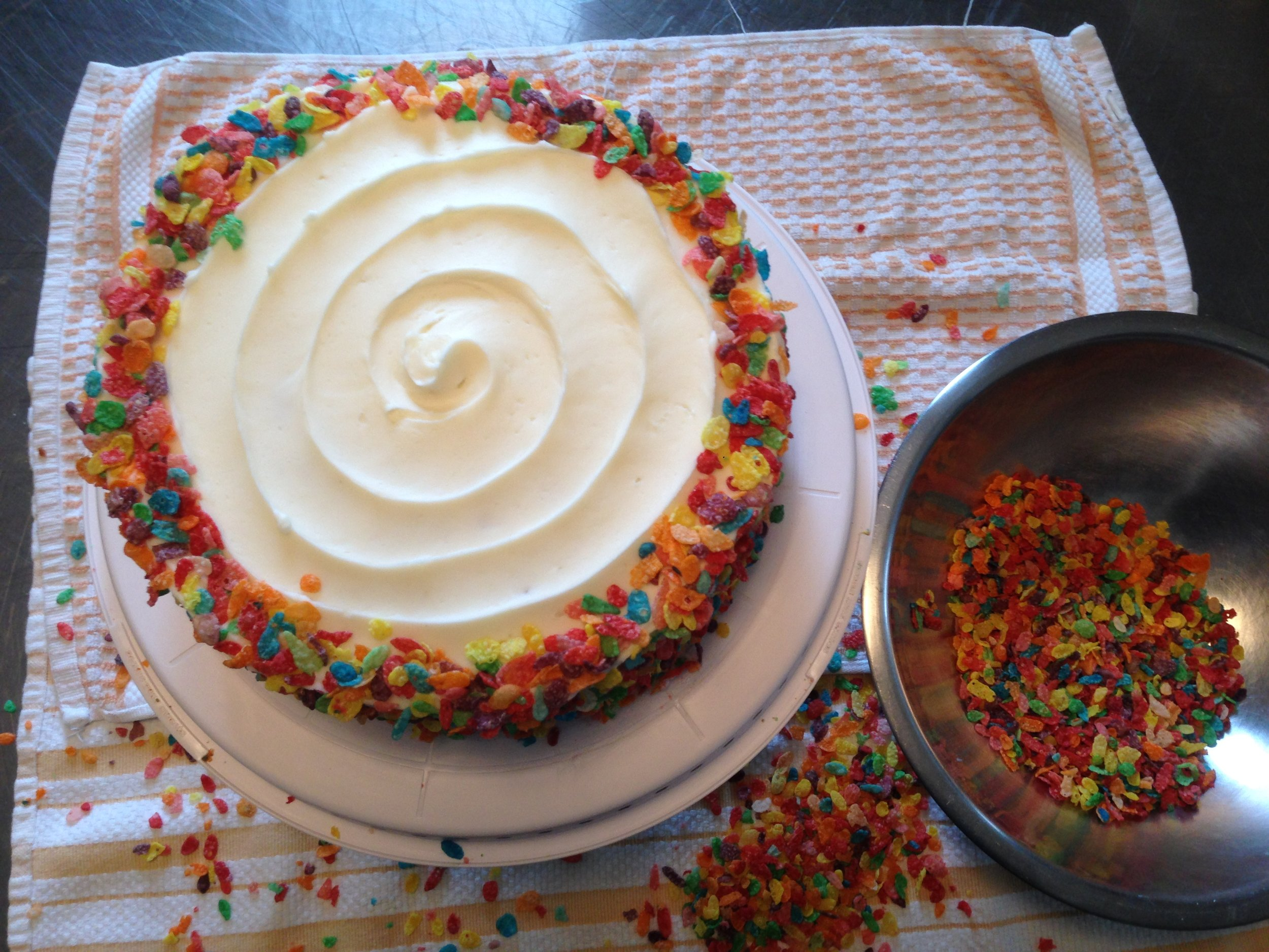 Fruity Pebble Cake cake getting adorned with sugary cereal goodness.