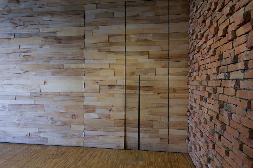 interior_ walls and doors made off discarded wood from sawmills, the recoverd brick from the burnt houses and the industrial parquet flooring.jpg