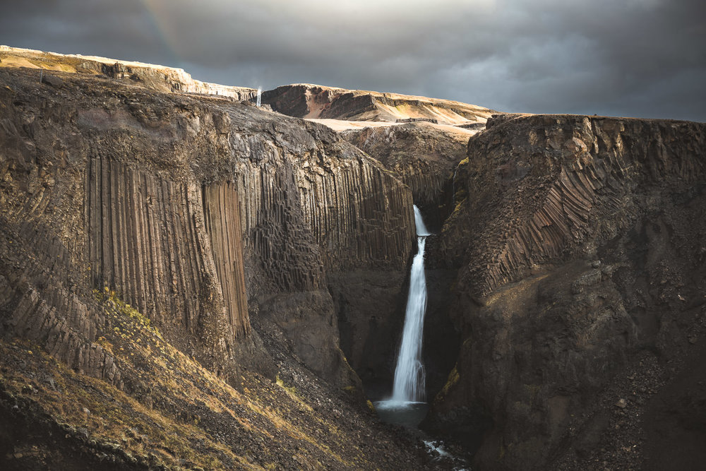 Litlanessfoss with Hengifoss on the background and a rainbow, snapped by @snapzak