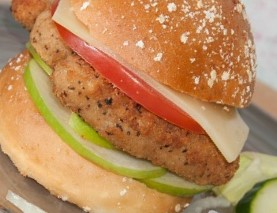 Chicken burger on a gluten free bun topped with millet flakes