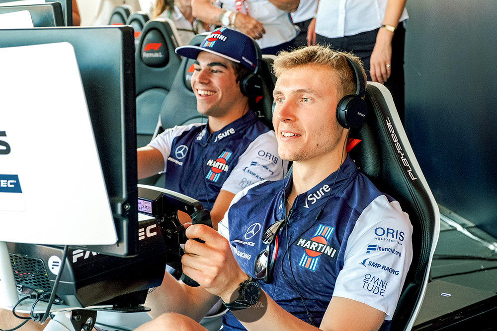 Sergey and his team-mate Lance go head-to-head on the simulators in the F1 Fan Zone
