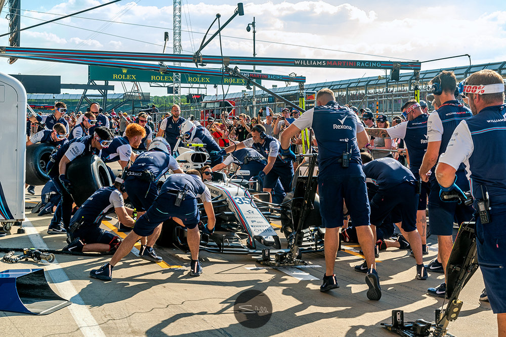 The Williams pitcrew practice their pitstops in the heat of the day in front of the Silverstone fans, with deputy Team Principal Claire Williams in the drivers seat