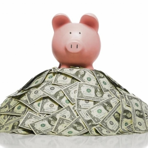 Piggy Bank Standing on Heap of Cash