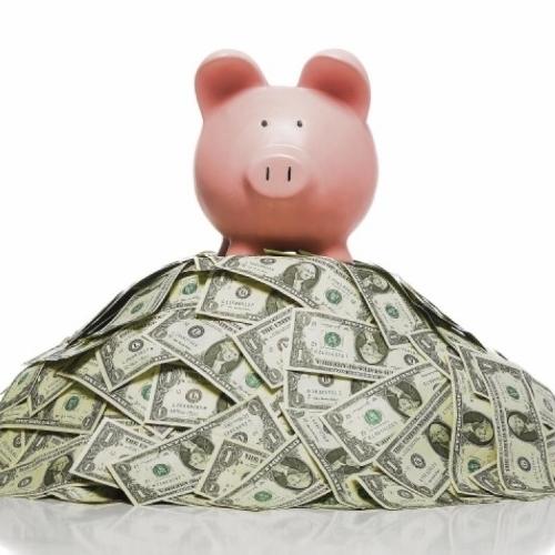 piggy bank stands on heap of cash