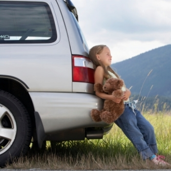 Young Girl Leaning Against Car