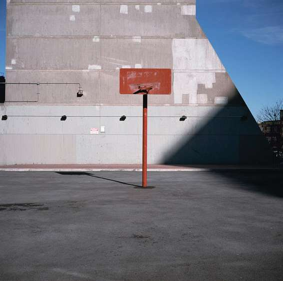 Basketball court with one of Air Right's windowless concrete walls behind it. (© Charles Johnstone, 2011)