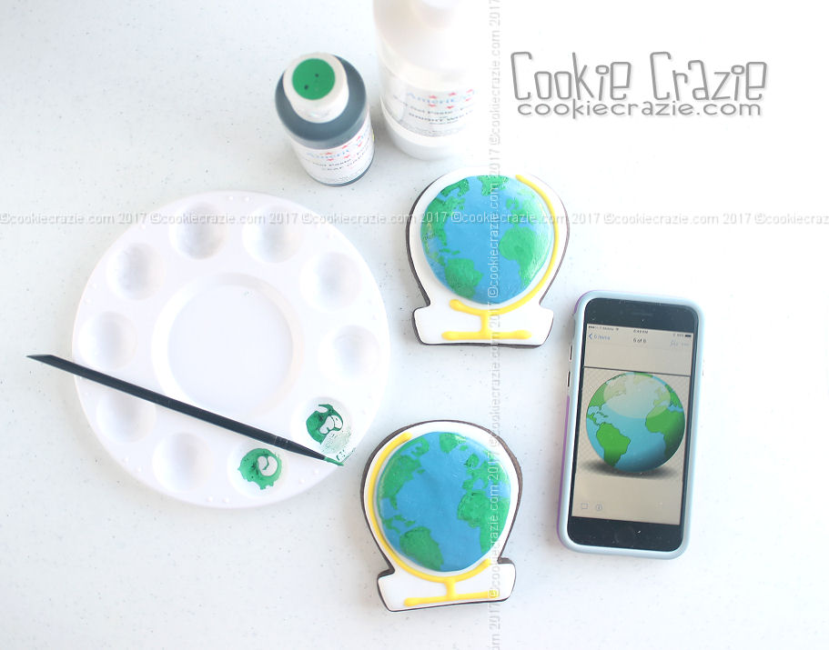 After the blue globe has dried for a few hours, use a map of the world to paint a rough outline of some of the continents with green glaze.