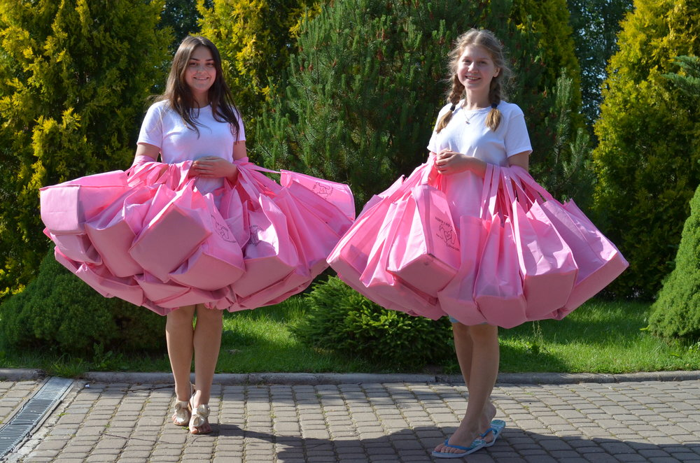 Each lady received a bright pink bag filled with lots of goodies. Here's two of the awesome workers who collected up all the bags to hand out to the women on the first day. (Isn't it cool how the bags create a pretty skirt effect on each of the girls/ :))
