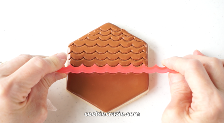 After the hexagon has dried for approximately 2 hours, use the  scalloped edger from SweetSugarBelle's Shapeshifter's set  to create rows of feather marks down the cookie as seen in the photo and video.