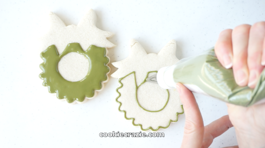 Outline and flood the main wreath with green glaze.