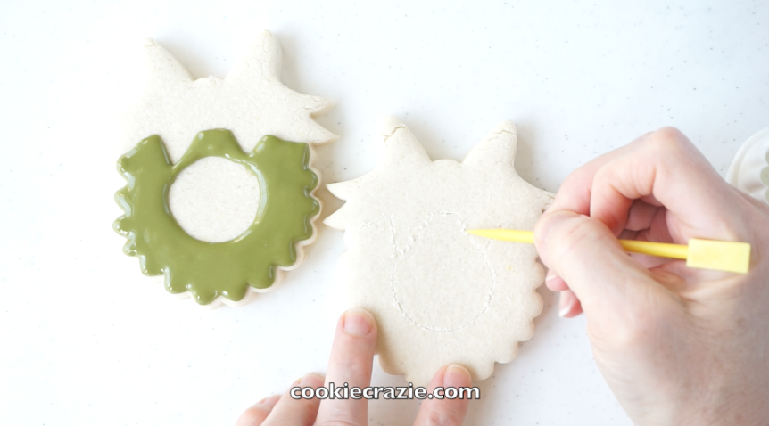 Once the cookie is baked and cooled, use a  boo boo stick  or toothpick to etch lightly on the cookie surface, making a circle in the middle and an outline of the bow portion. [This will give you a reference of where to pipe the glaze.]