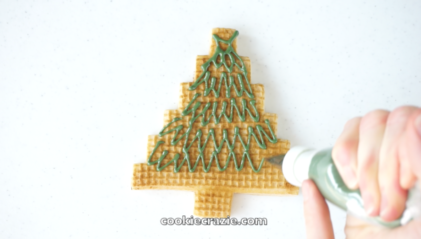 For the first design, cover the tree portion of the cookie with green glaze using random zig zag lines. (see photo and video for more visual details)