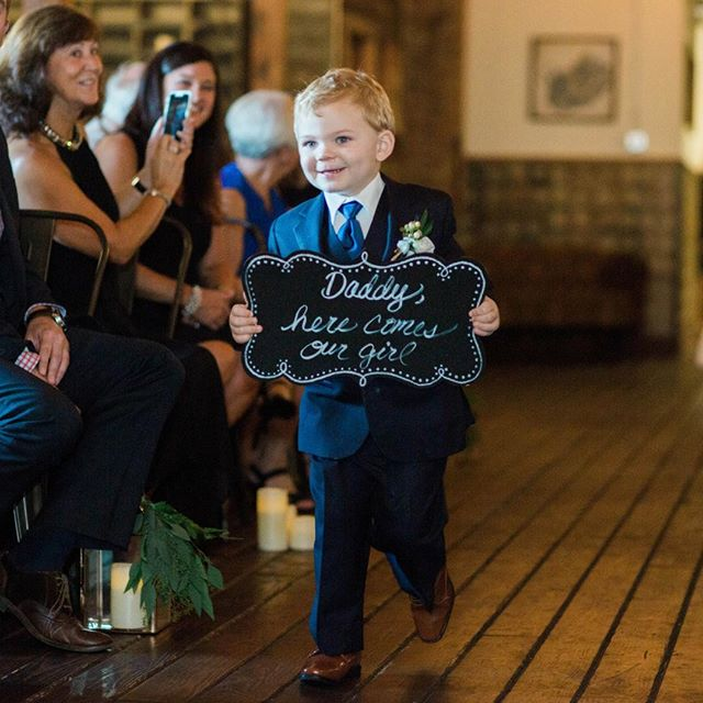 This little man is so excited he's practically running down the aisle! That sign and those dimples just make the photo that much more precious! Comment 👇🏻if you had kiddos walking down the aisle with signs. What did they say? #cutiepie @maryrosephotography @thehaight