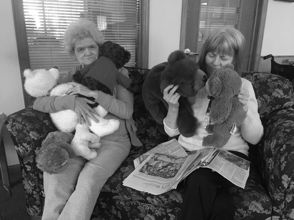 senior adults hug stuffed bears