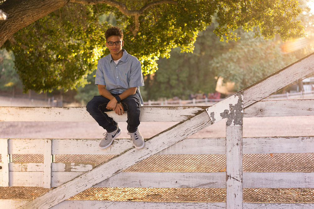 high school graduate sitting on fence-Danville outdoor photography