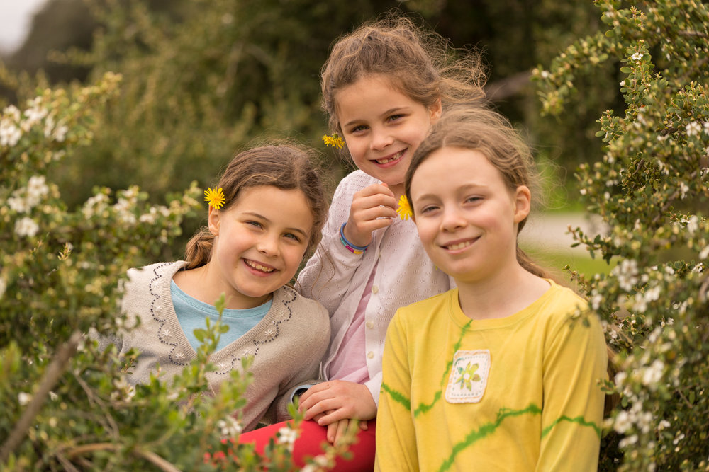 3 girls with flowers smiling-Oakland children's photographer