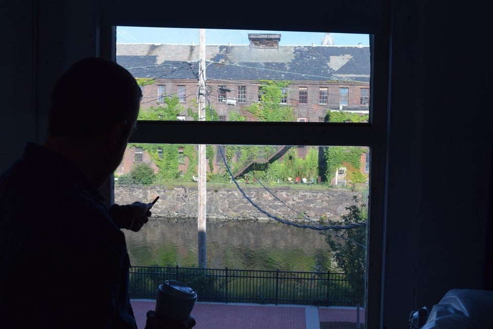 Ray Larrow looks out the window of his studio at a city canal and a vacant, ivy-covered mill. His paintings depict both the beauty and the emptiness of city spots.. (Patrick O'Connor photo)
