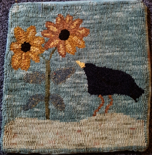 A primitive little crow checking out the sunflowers.  Hooked by me.