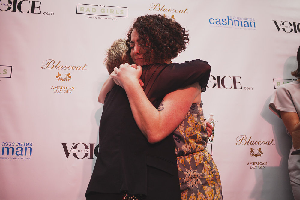 Educator of The Year Eileen R. Heisman hugs presenter Lansie Sylvia at The Rad Awards. April 18. 2015. The Dreaming Building. Chris Fascenelli/Rad-Girls.com.