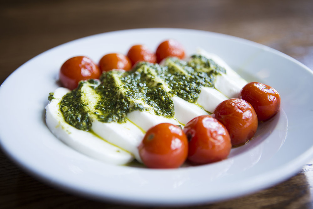 Caprese salad with tomato, basil, pesto, fresh mozzerella, olive oil, sea salt and cracked pepper at Pizza Brutta on May 17, 2016 in Middleton, WI.
