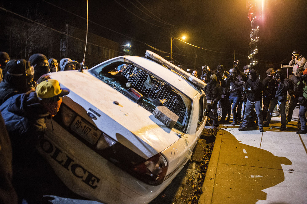 Protesters vandalize a police vehicle outside the Ferguson City Hall on Nov. 25, 2014 in Ferguson, MO.